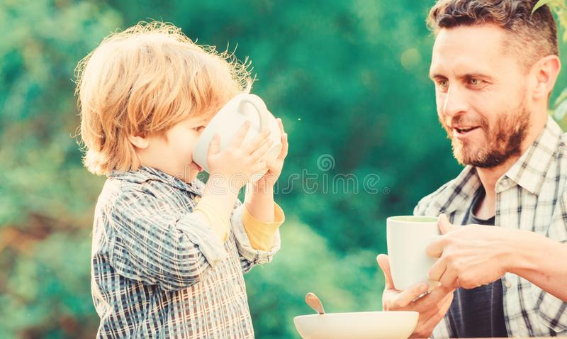 Father and son eat outdoor. healthy food. Family day bonding. small boy child with dad. they love eating together. Weekend breakfast. organic and natural food royalty free stock photo