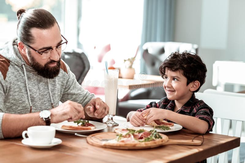 Father and son eating extremely yummy pizza with bacon and cheese. Yummy pizza. Bearded father and cute son eating extremely yummy pizza with bacon and cheese stock images