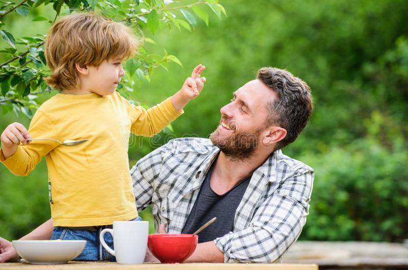 Father and son eating outdoor. summer picnic. Morning breakfast. healthy food and dieting. Childrens day. happy fathers royalty free stock photo
