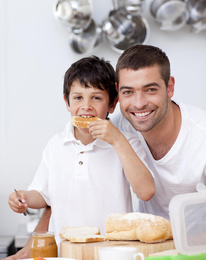 Father and son eating a toast. In the kitchen royalty free stock photos
