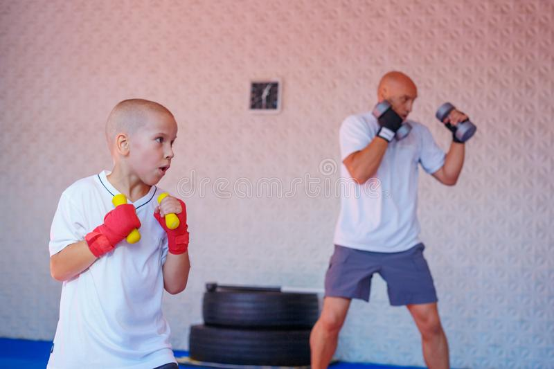 Father and son are engaged in the gym royalty free stock photography