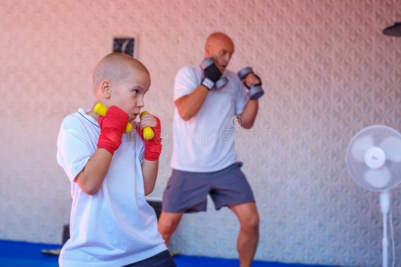Father and son are engaged in the gym royalty free stock image