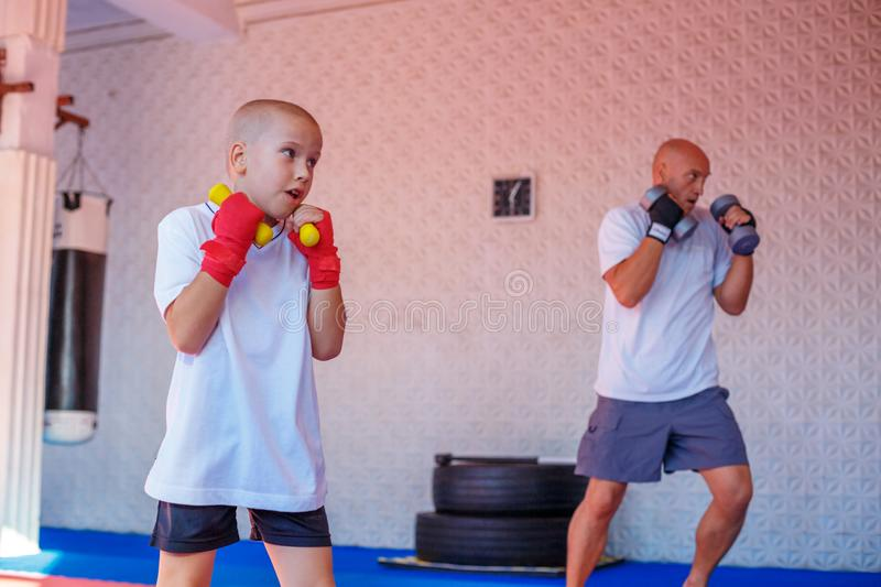 Father and son are engaged in the gym royalty free stock photo