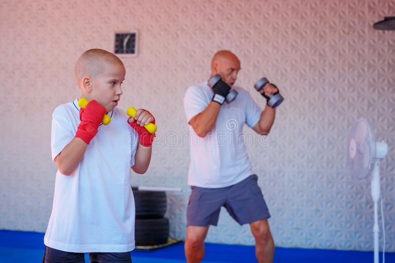 Father and son are engaged in the gym stock photo
