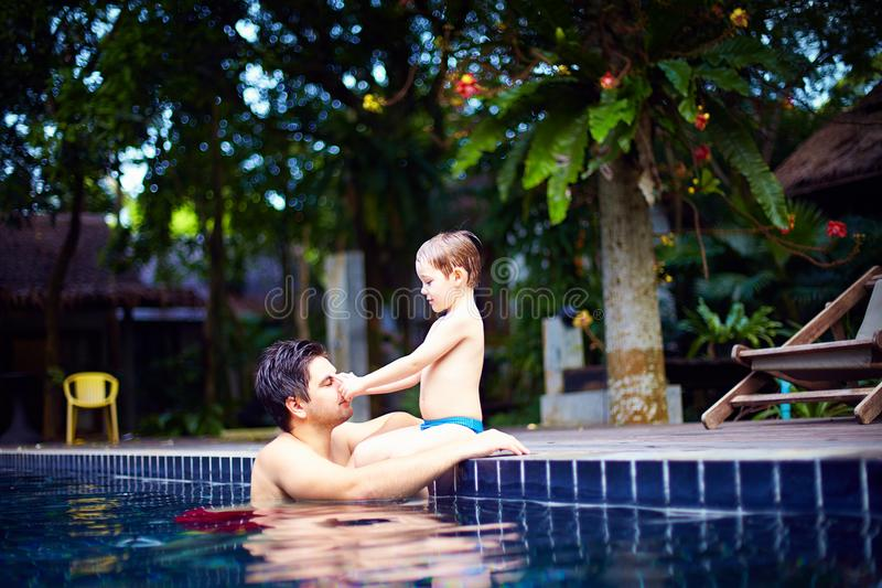 Father and son enjoy relaxing in the pool at quiet getaway. Cheerful father and son enjoy relaxing in the pool at quiet getaway stock photos