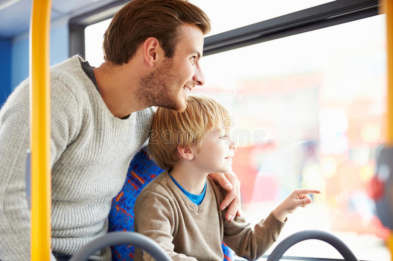 Father And Son Enjoying Bus Journey Together. Looking Out Window Smiling royalty free stock photos