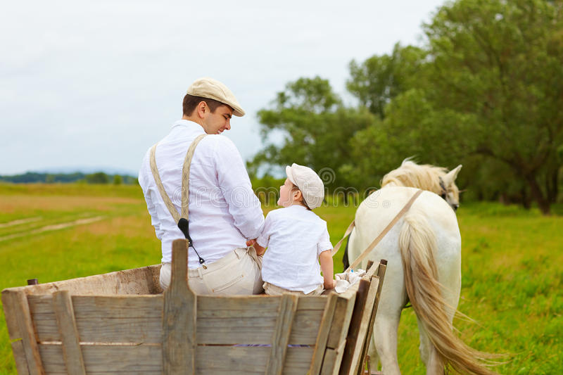 Father and son, farmers ride a horse cart royalty free stock photo