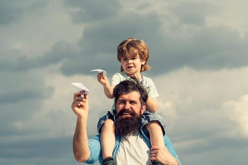 Father and son. Father giving son ride on back in park. Father and son in the park. Freedom to Dream - Joyful Boy. Playing With Paper Airplane royalty free stock photo