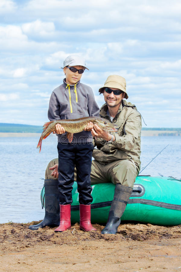 Father and son fish at boat stock photo
