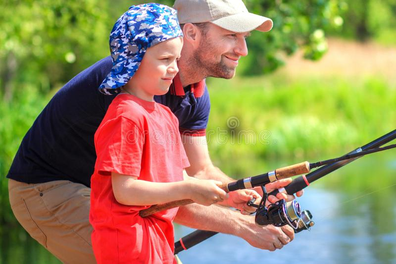 Father and son on fishing. Family catching fish on lake shore. Happy family with fishing rods. Fishermen stock photo