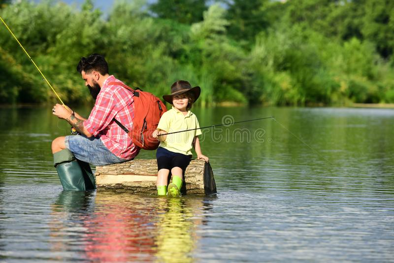 Father and Son fishing - Family Time Together. Happy father and son fishing in river holding fishing rods. royalty free stock photo