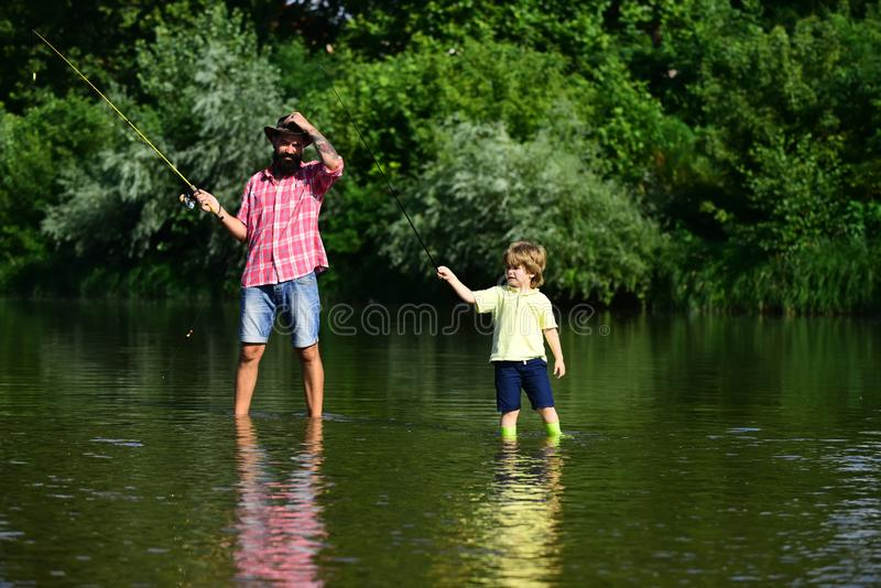 Father and son fishing. Father with his son on the river enjoying fishing holding fishing rods. Father and son fishing. Father with his son on the river stock photography