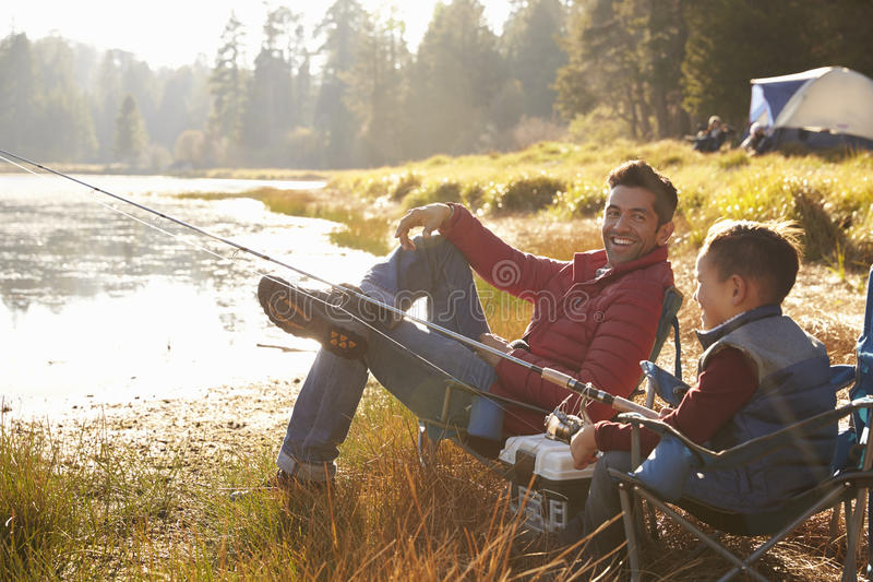 Father and son fishing by a lake, dad looks to camera stock images