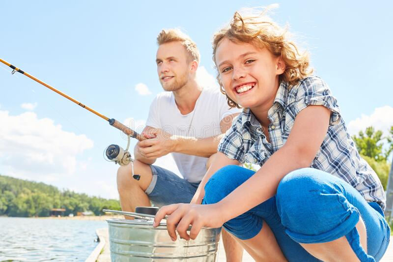 Father and son are fishing at the lake in summer stock photo