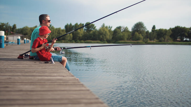Father and son fishing off a wooden jetty royalty free stock image
