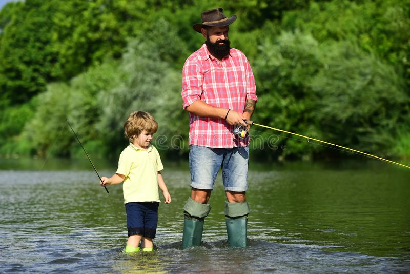 Father and son fishing and relaxing while enjoying hobby. Anglers. Fishermen father and son fishing in a river with a royalty free stock photos