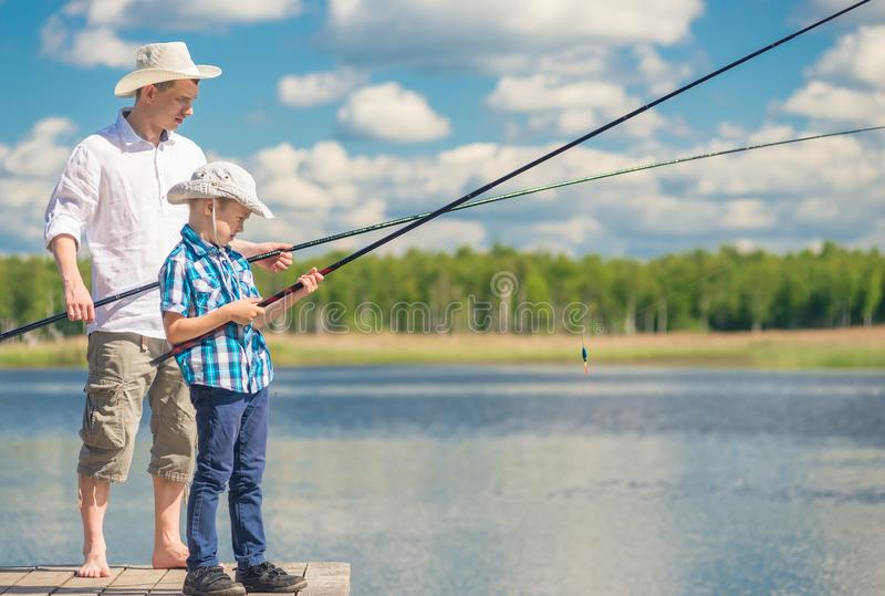 Father and son with fishing rods on a wooden pier near the lake royalty free stock images