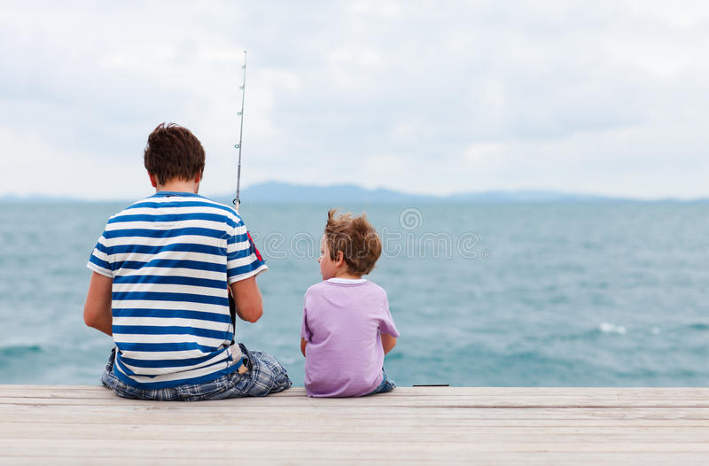 Father and son fishing together royalty free stock photography