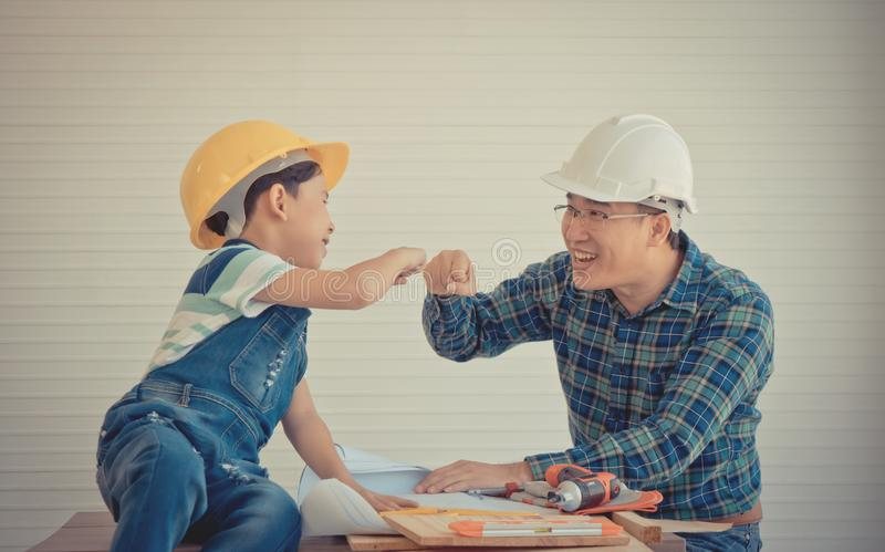 Father and Son fist bump success concept in construction industry concept in vintage tone stock photography