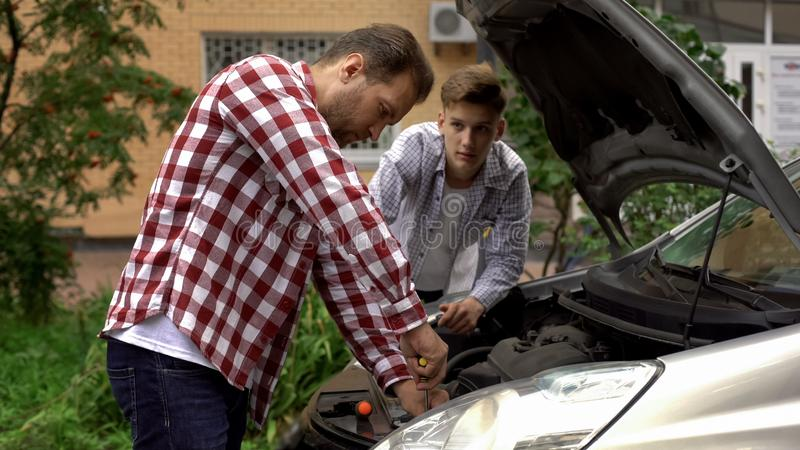 Father and son fixing car, dad teaching teen boy to repair engine, role model royalty free stock image