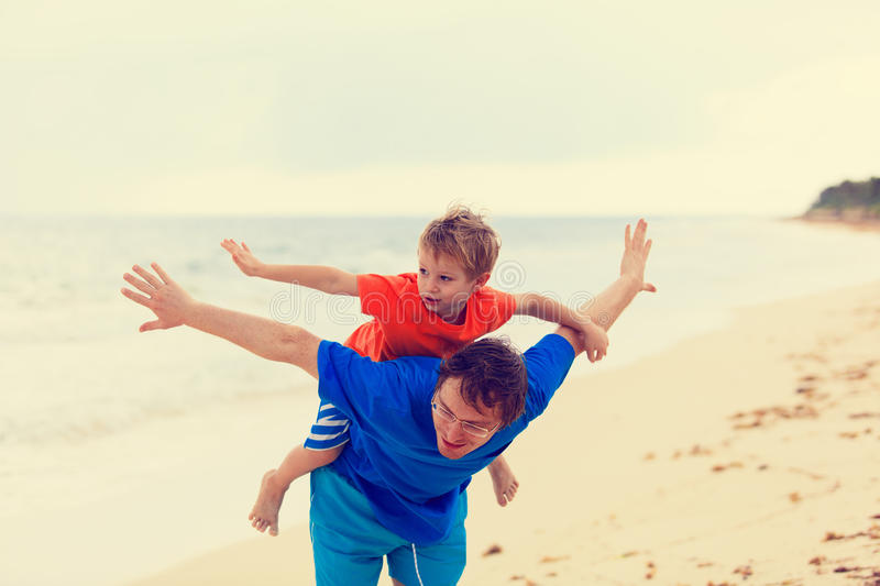 Father and son flying at the beach royalty free stock photos