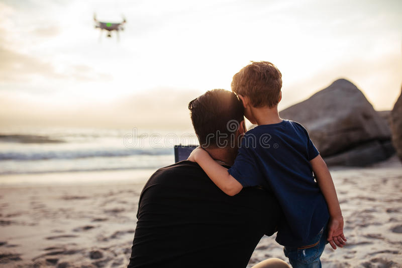 Father and son flying drone at the sea shore royalty free stock photos