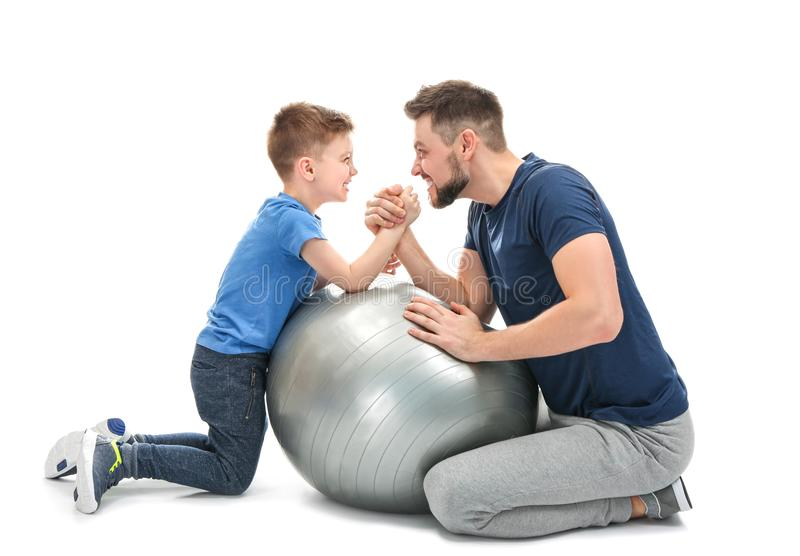 Father and son during friendly arm wrestling competition. On white background stock photos