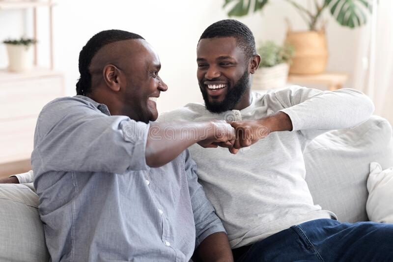 Father-Son Friendship. Black Millennial Guy Bumping Fists With Senior Dad At Home royalty free stock images