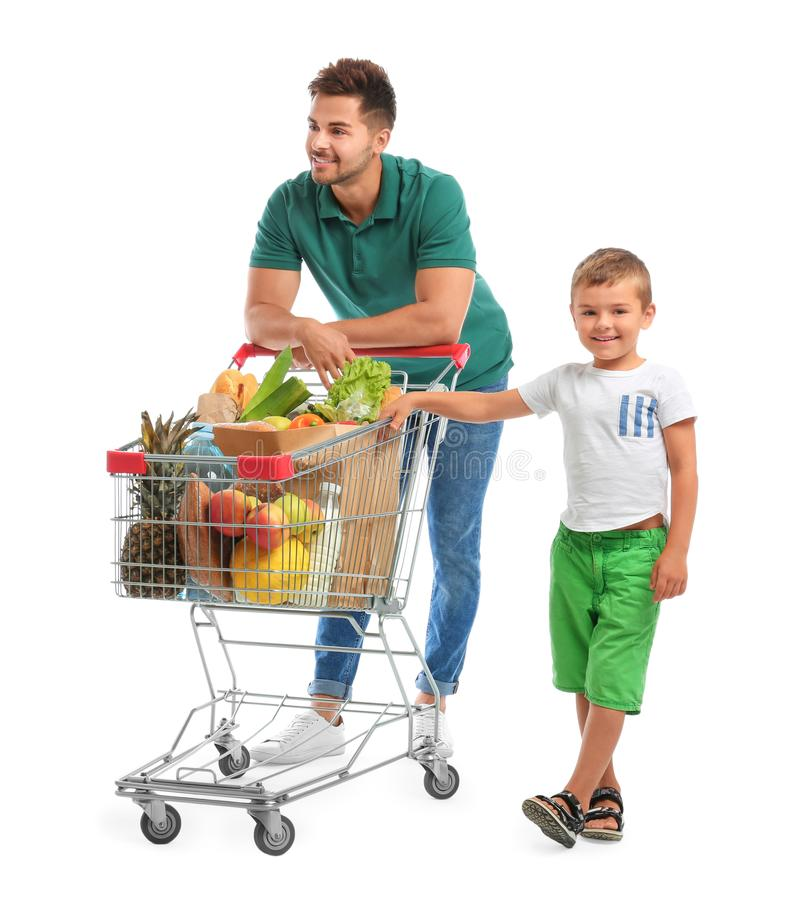 Father and son with full shopping cart on background royalty free stock image