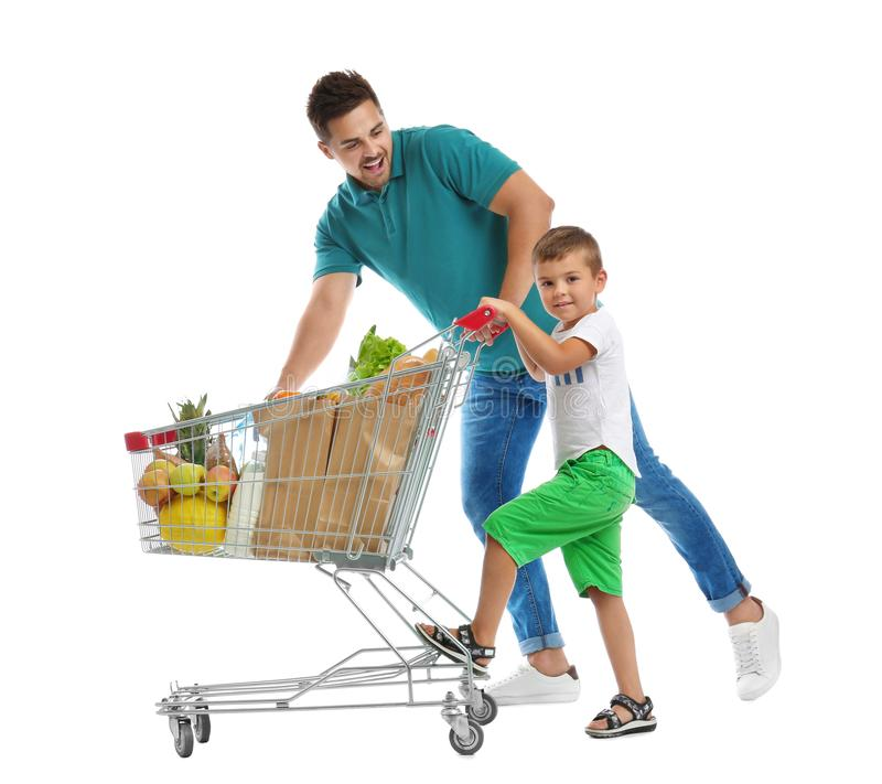 Father and son with full shopping cart on background. Father and son with full shopping cart on white background stock photos