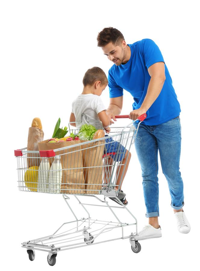 Father and son with full shopping cart on background stock photo