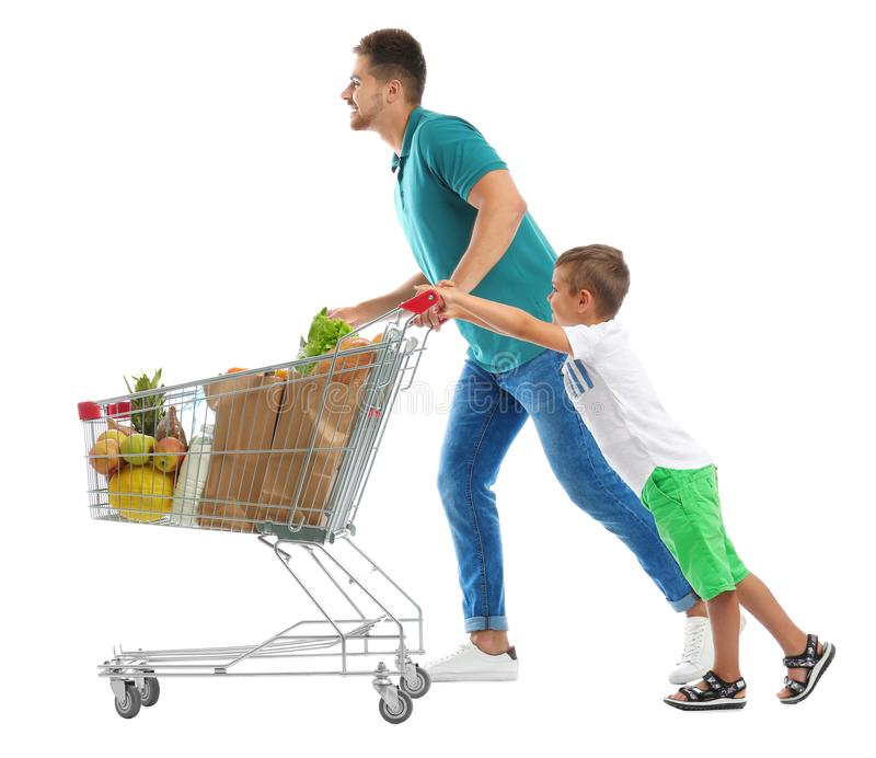 Father and son with full shopping cart on background stock photography