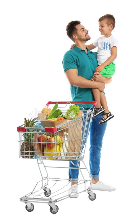 Father and son with full shopping cart on background. Father and son with full shopping cart on white background royalty free stock image