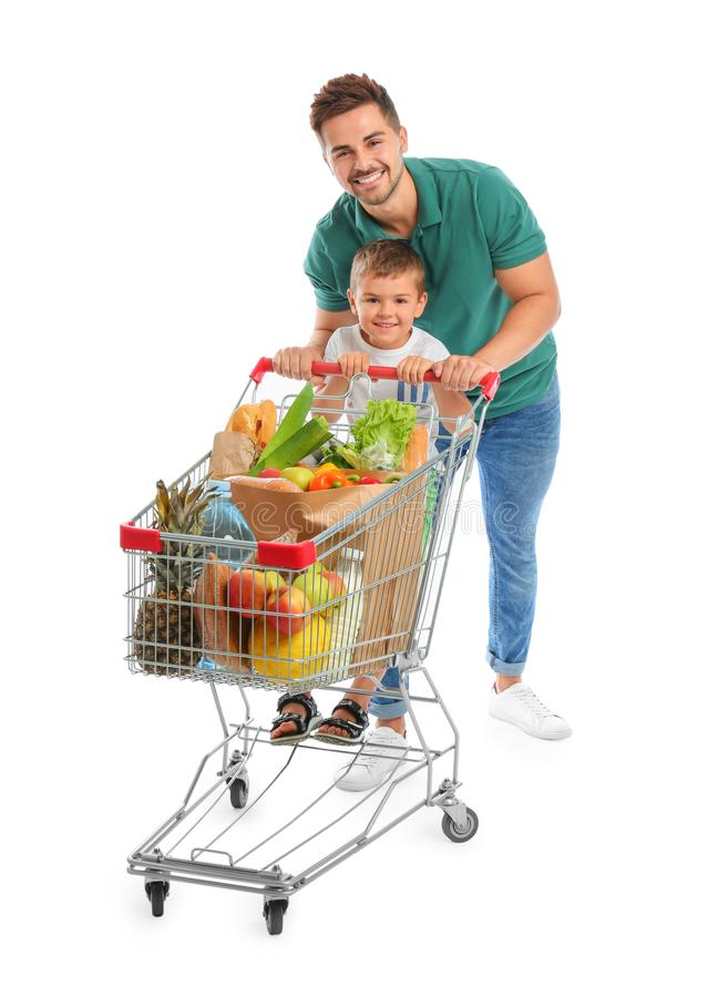 Father and son with full shopping cart on background royalty free stock photography