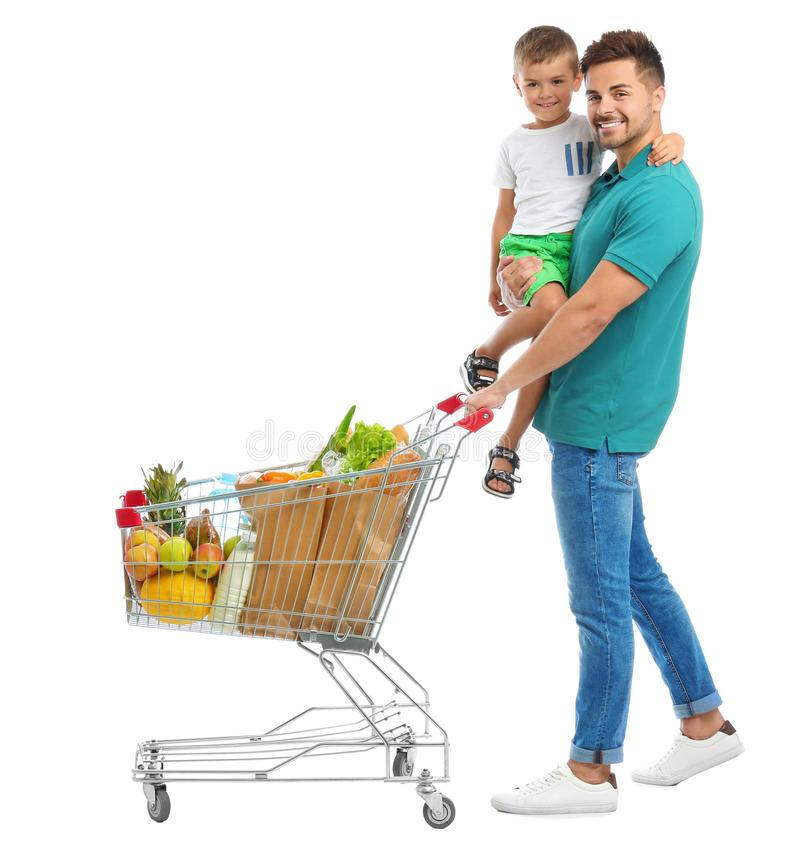 Father and son with full shopping cart on background. Father and son with full shopping cart on white background stock image