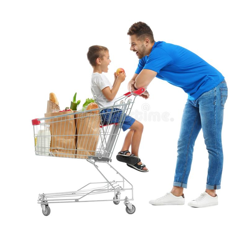 Father and son with full shopping cart on background royalty free stock photo