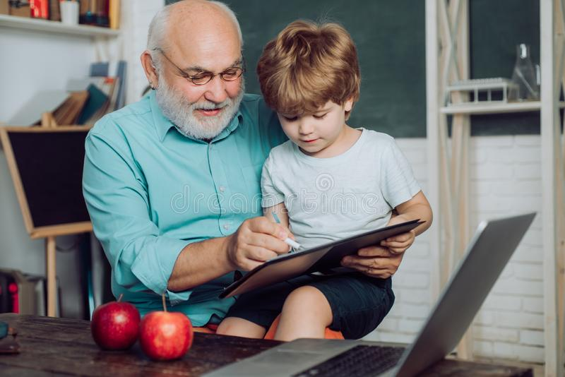 Father and son - generation people concept. Kid with old teacher learning in class on background of blackboard. Little royalty free stock image