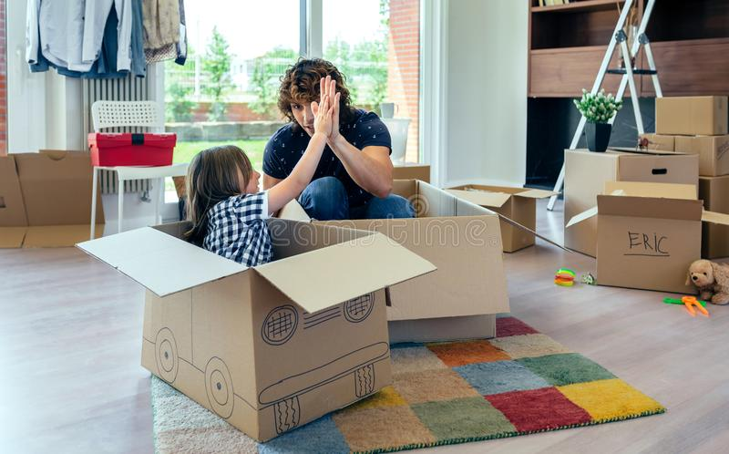 Father and son giving five after cardboard car racing. Father and son giving five after playing car racing with cardboard boxes royalty free stock image