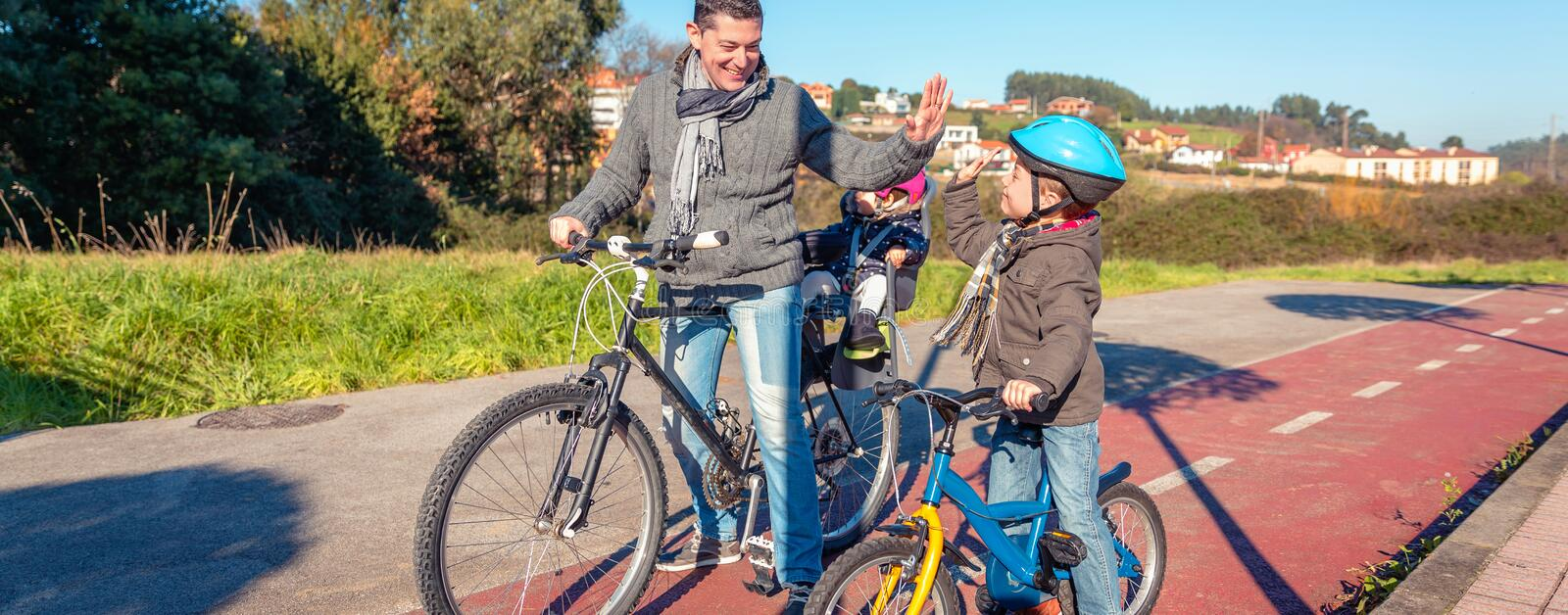 Father and son giving five by success riding bicycle royalty free stock images