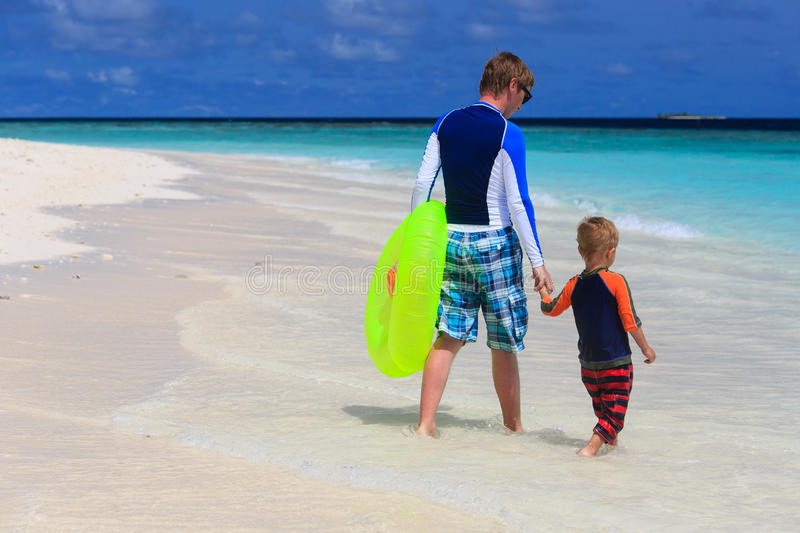 Father and son go swimming at the beach royalty free stock image
