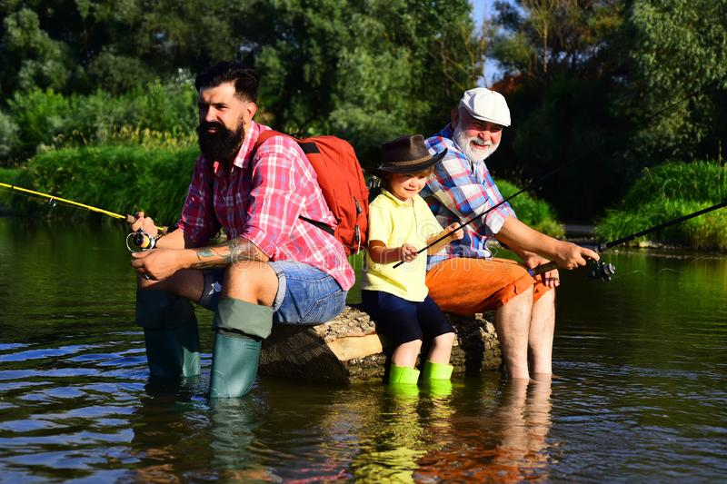 Father, son and grandfather fishing. Men day. Great-grandfather and great-grandson. Fly fishing for trout. Father and. Son fishing stock images