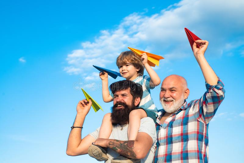 Father son and grandfather playing - family time together. Three different generations ages: grandfather father and royalty free stock image