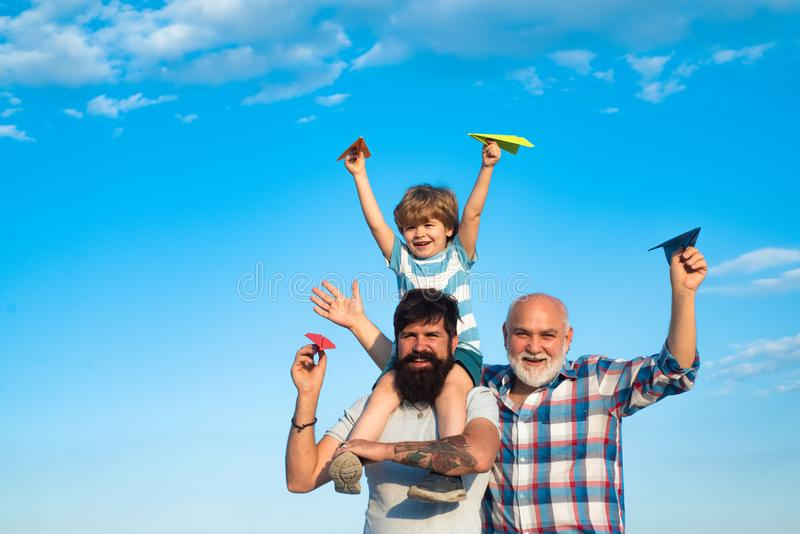 Father son and grandfather relaxing together. Freedom to dream - joyful kid playing with airplane against the sky - royalty free stock image