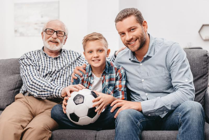 Father, son and grandfather sitting together on couch in living room royalty free stock photography