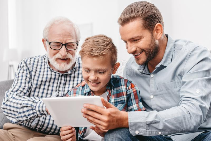 Father, son and grandfather sitting together on couch in living room and looking at digital stock photo
