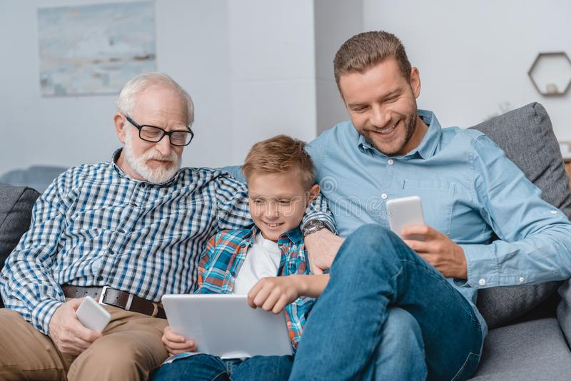 Father, son and grandfather sitting together on couch in living room with smartphones and digital tablet stock photos