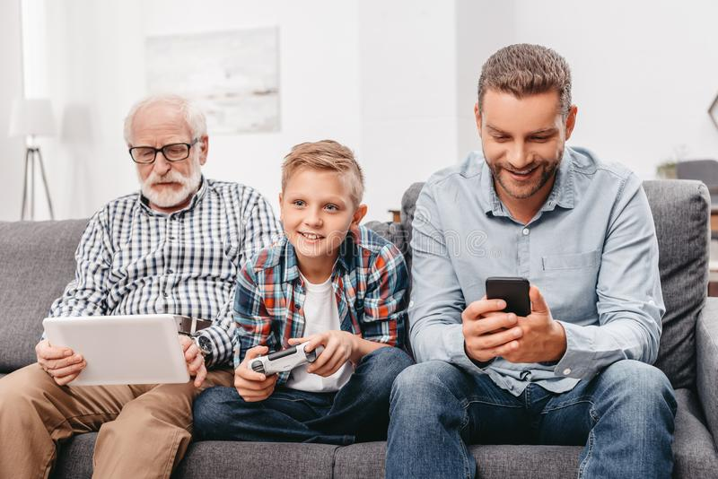 Father, son and grandfather sitting together on couch in living room using various royalty free stock photography