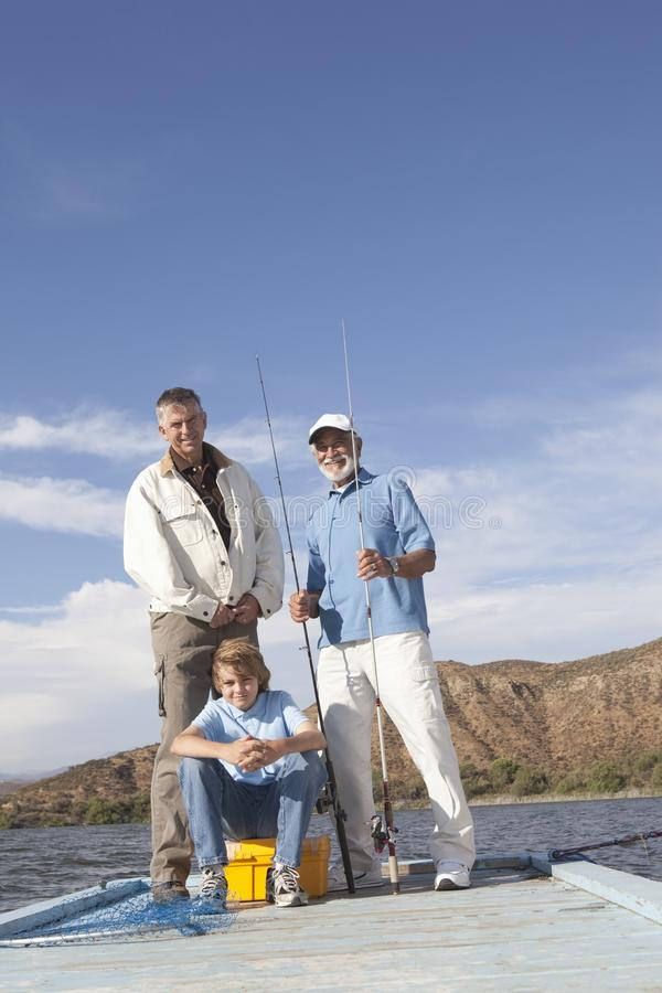 Father, Son And Grandson With Fishing Equipment. Full length of father, son and grandson with fishing equipment on a pier royalty free stock image