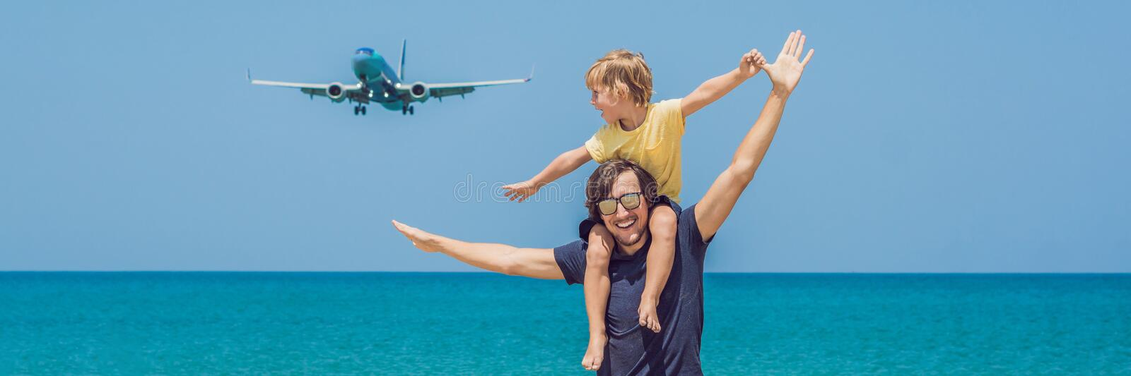 Father and son have fun on the beach watching the landing planes. Traveling on an airplane with children concept BANNER, long form stock images