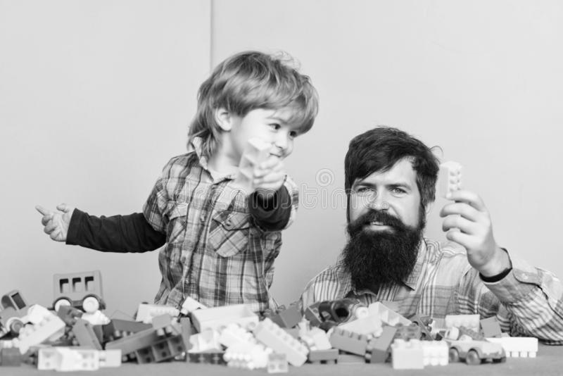Father and son have fun. Bearded hipster and boy play together. Dad and child build plastic blocks. Importance of. Playing together. Child care concept. Happy stock photography